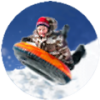 boy up in the air on a tube sledding in the snow7